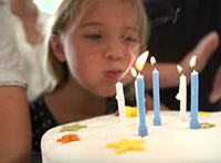 stock-footage-little-girl-blows-out-candles-on-birthday-cake-at-party-slow-motion-sequence